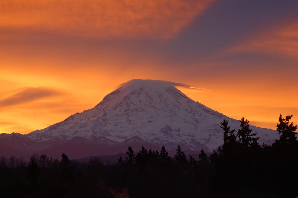 The sunrise swelling behind Mt. Rainier.